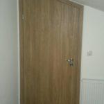 Przerobione drzwi zamontowane pod skośnym sufitem.